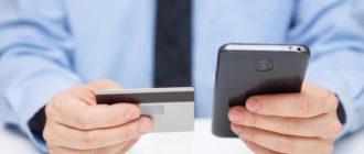 Человек с телефоном и картой банка